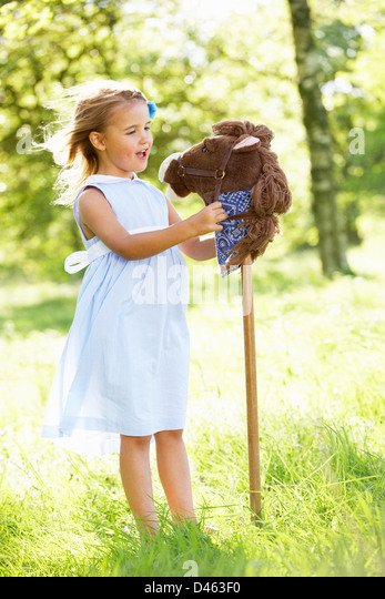Young Girl Playing With Hobby Horse In Summer Field - Stock Image