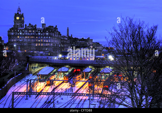Waverley station at dusk in winter snow, Princes St, Edinburgh, Scotland, UK @HotpixUK - Stock Image