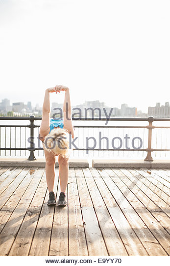 Woman stretching on bridge, Montreal, Quebec, Canada - Stock Image
