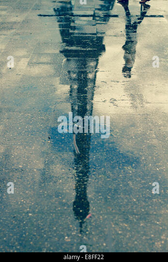 Reflection of man walking past Eiffel Tower in a puddle, Paris, France - Stock-Bilder