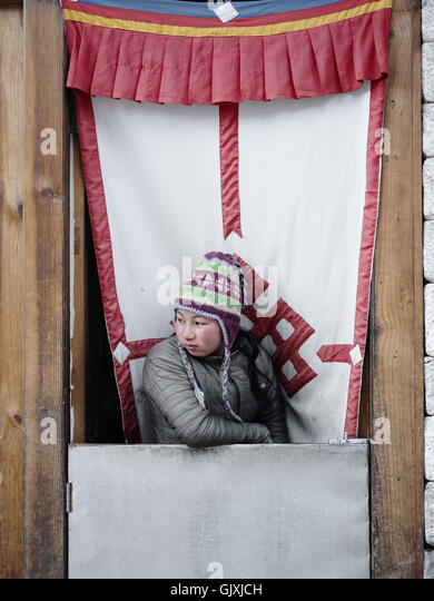 A Nepalese woman looks out the window of her shop in Namche, Nepal - Stock Image