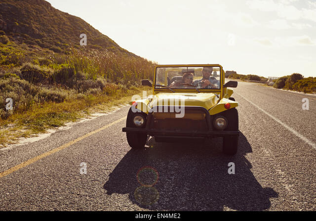 Young couple driving in a car on a open road. Young couple on road trip on summer day. - Stock Image