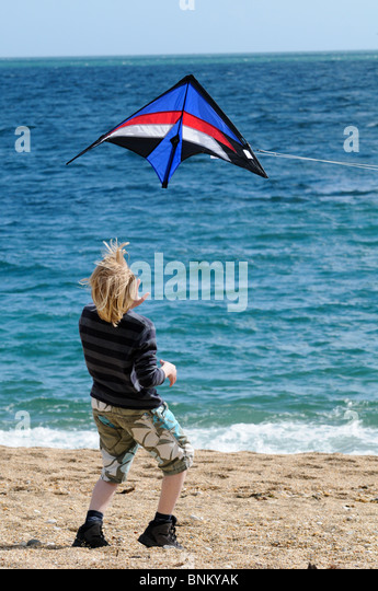 Boy leaning back and watching a kite flying just above his head on a sunny beach after he's just let go of it - Stock-Bilder