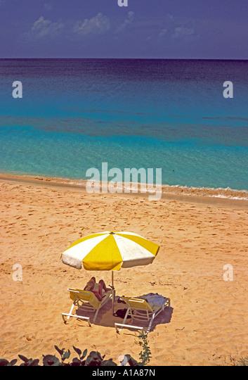 Anguilla beach couple umbrella on Mead's Bay beach - Stock Image