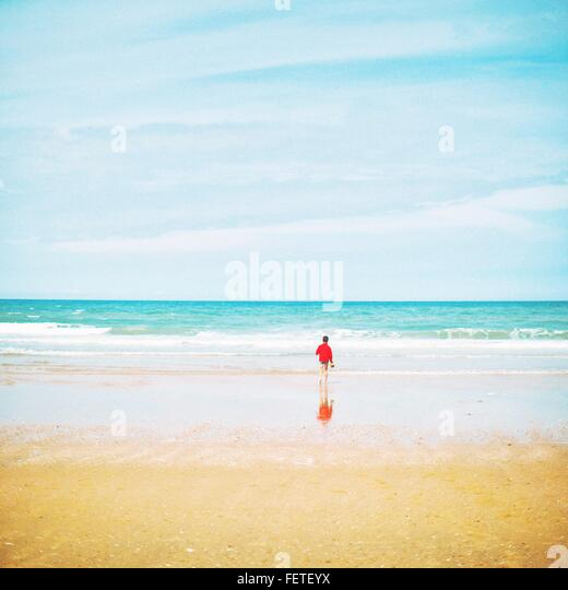 Rear View Of Person In Red Top, Turquoise Seascape, Sand In Foreground - Stock Image