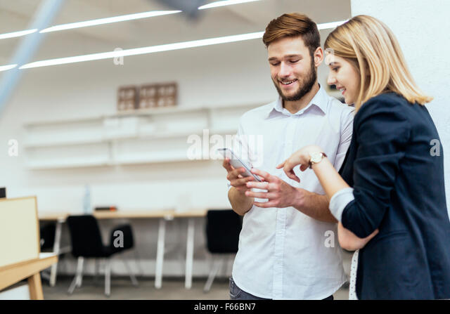 Colleagues laughing together in office during work - Stock Image