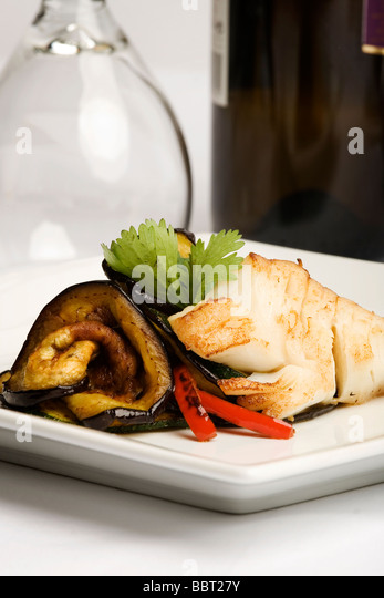 Plate of baked cod with eggplant and peppers - Stock Image