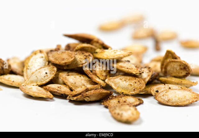 Roasted butternut squash seeds on white background - Stock Image