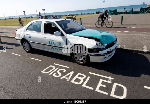A damaged cab, after a road accident, parked in a disabled bay - Stock Image