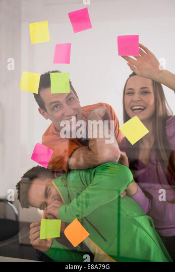 Three colleagues arguing deciding using post-ist - Stock Image