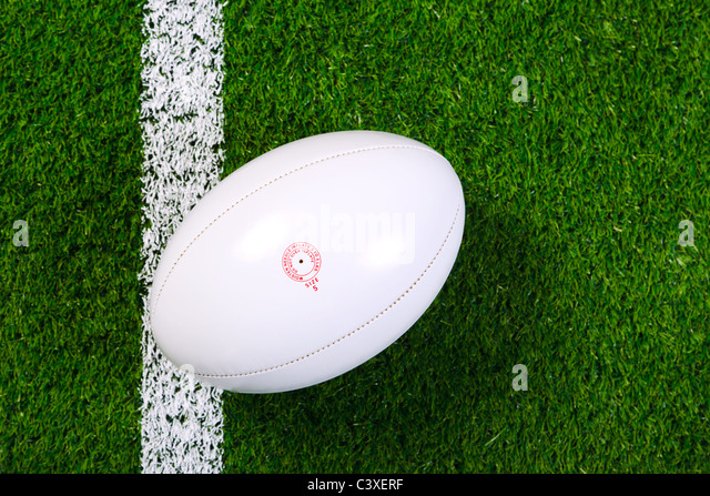 Photo of a rugby ball on a grass next to the white line, shot from above. - Stock Image