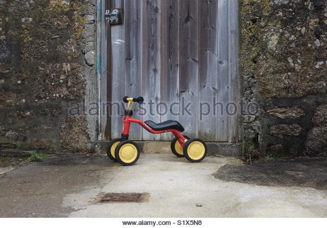 Child's tricycle against weathered barn door surrounded by weathered wall - Stock Image