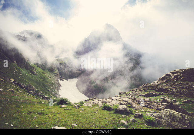 Rocky Mountains foggy Landscape with clouds and green valley Summer Travel serene scenic view - Stock Image