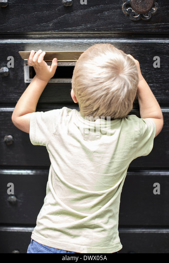 Rear view of little boy looking through mail slot of door - Stock Image