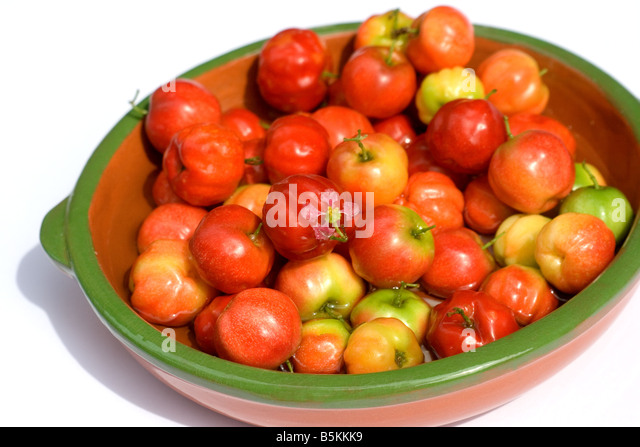 Acerola berries in a bowl on white background - Stock Image