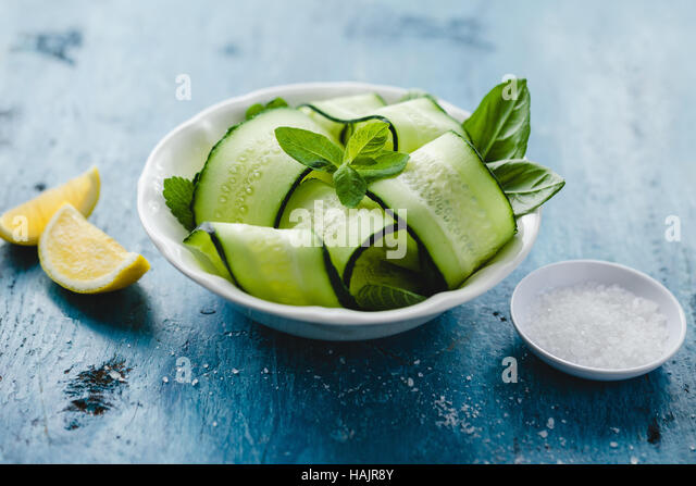 Bowl of fresh cucumber and mint salad with sea salt and lemon - Stock Image