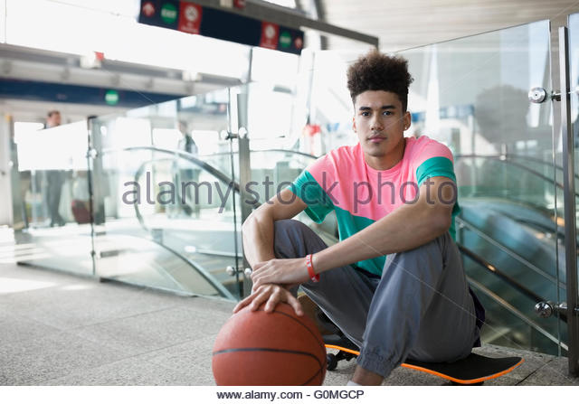 Portrait confident young man basketball skateboard train station - Stock Image