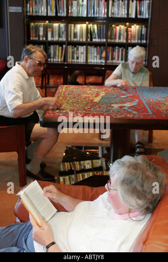 Puerto Rico Atlantic Ocean Holland America Line ms Noordam Explorations Cafe woman reads jigsaw puzzle - Stock Image
