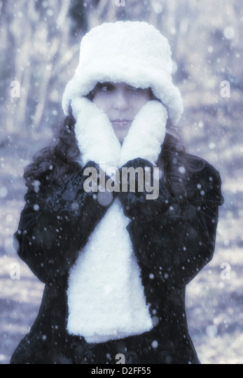 a woman with a black coat, white gloves, scarf and hat outside during snowfall - Stock Image