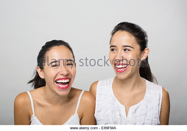 Brunette twin sisters laughing - Stock-Bilder