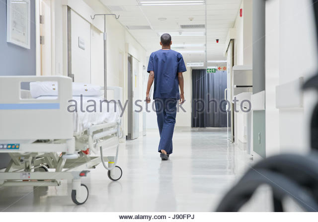 Rear View Of Male Doctor Walking Along Hospital Corridor - Stock-Bilder