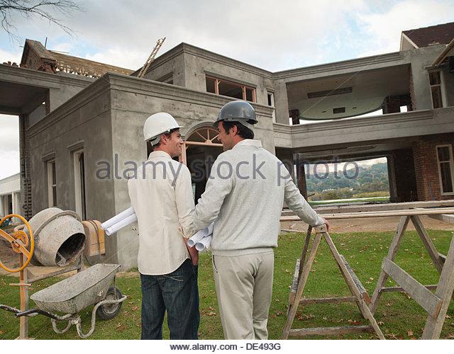 Architects  holding   blueprints outside house under construction - Stock Image