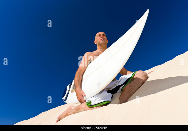 Surfer sitting on dune. - Stock Image