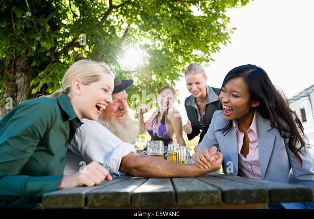 Germany, Bavaria, Upper Bavaria, Asian woman and bavarian man in beer garden, arm wrestling - Stock-Bilder
