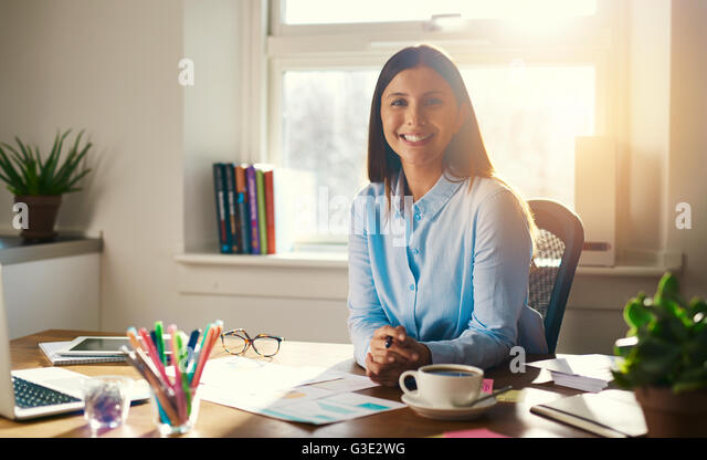 Confident business woman sitting at desk with folded hands smiling at the camera - Stock Image
