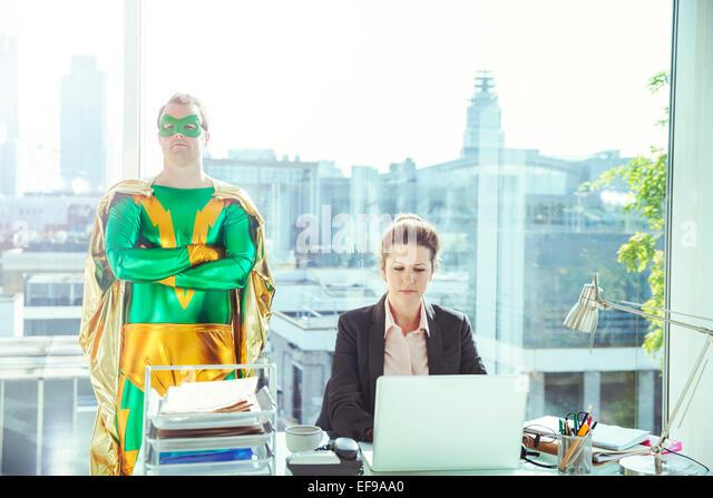 Superhero standing near businesswoman working in office - Stock Image
