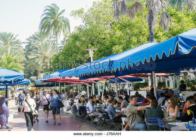 Miami Beach Florida Lincoln Road pedestrian mall alfresco dining restaurant umbrellas shoppers The Cafe at Books - Stock Image