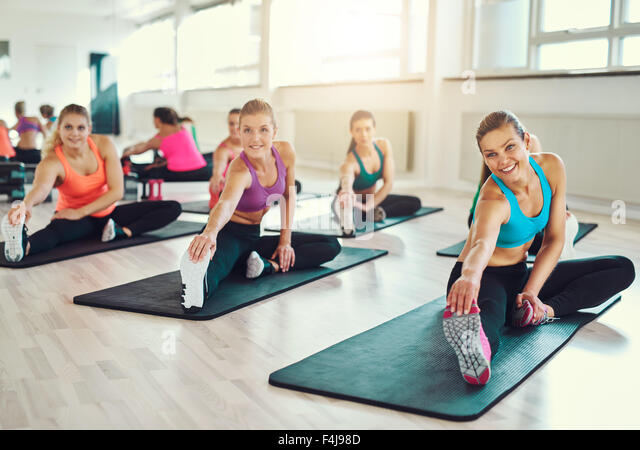 Group of young women in aerobics class at a gym doing stretching exercises to tone their muscles in a health and - Stock Image