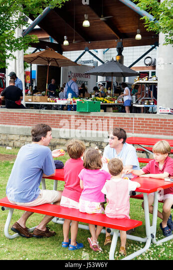 Little Rock Arkansas River Market man men boy girl children child family dad red picnic bench eat childcare family - Stock Image