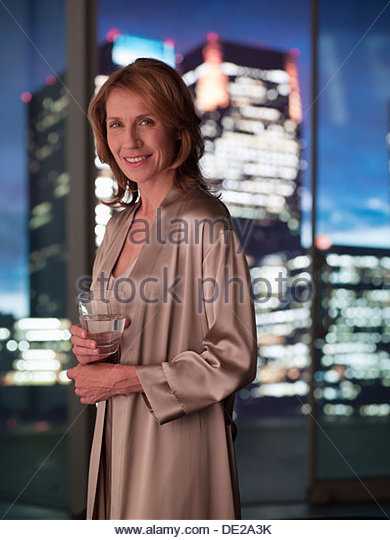 Woman in nightgown drinking with cityscape in background - Stock-Bilder