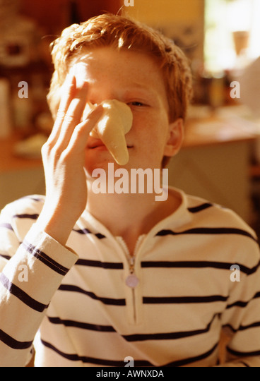 Child holding fake nose to face, portrait - Stock Image