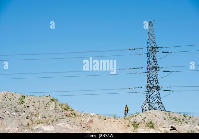 Man standing under electricity pylon - Stock-Bilder