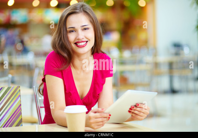 Pretty shopper taking repose, shopping being done - Stock Image