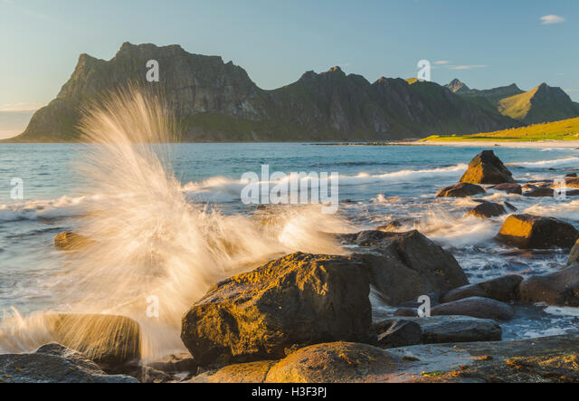 Rocks in evening light with warm light shining on them, waves coming to the shore and splashing on the rocks, Uttakleiv, - Stock Image