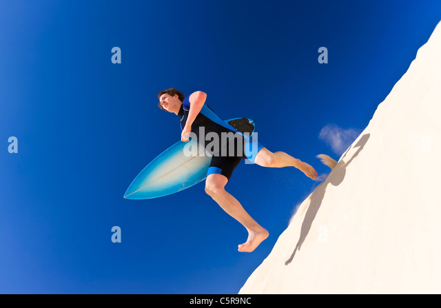 Surfer running across sand dunes to the sea. - Stock-Bilder