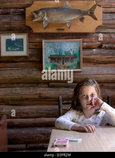 Girl sitting at the table in a log cabin - Stock Image