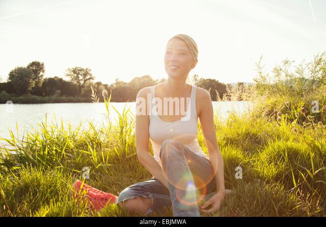 Young woman sitting on grassy riverbank, Danube Island, Vienna, Austria - Stock Image