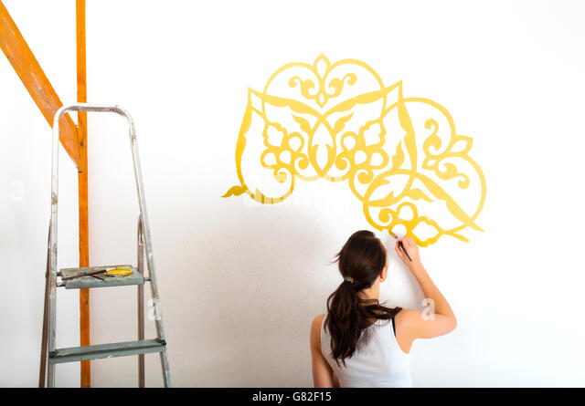 Girl painting on a wall - Stock Image