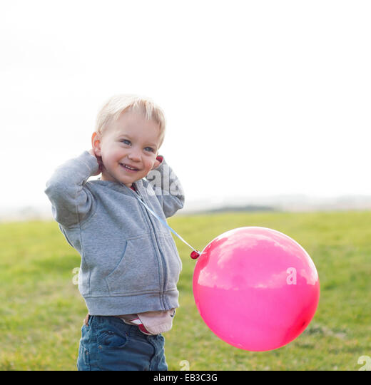 Boy holding a pink balloon - Stock Image