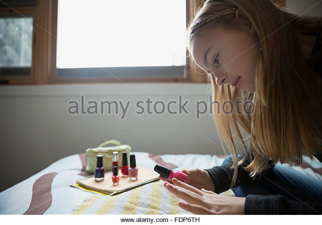 Girl painting fingernails on bed - Stock Image