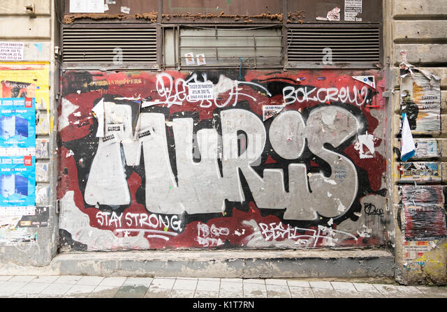 Istanbul, Turkey - April 18, 2017:  Closed shop exterior with metal door covered with colorful graffiti near Istiklal - Stock Image