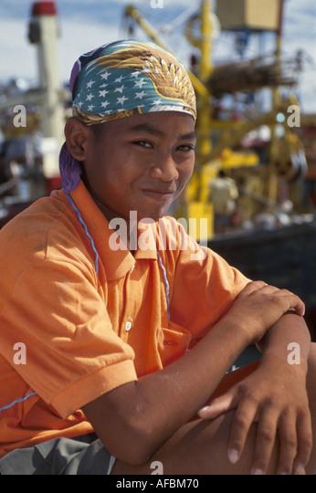 Malaysia Borneo Sabah Kota Kinabalu boy works on boats in harbor by Jalan Tun Fuad Stephens - Stock Image