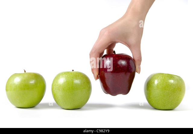 Person taking a red apple from a row of green apples Choice concept Isolated on white background - Stock Image
