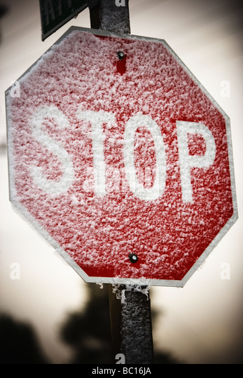 Snow covered stop sign. - Stock Image