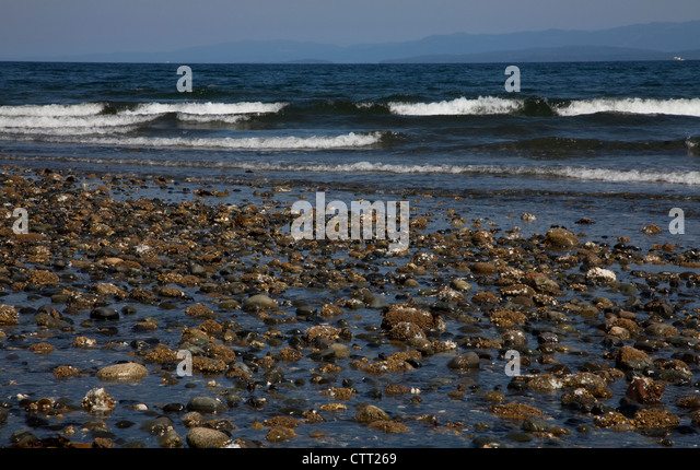 Rathtrevor Park Beach, Vancouver Island, BC with the tide out and the Pacific Ocean crashing into the rocks on the - Stock Image