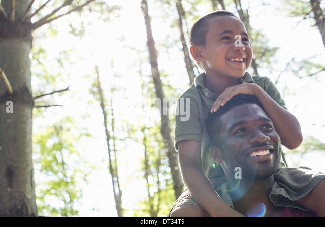 A boy sitting on his father's shoulders - Stock-Bilder